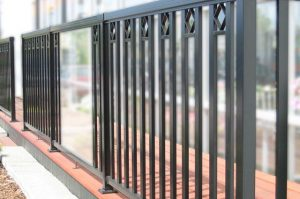 Large Glass Panel with Black Pickets and Decorative Spacer Aluminum Railing on a low platform