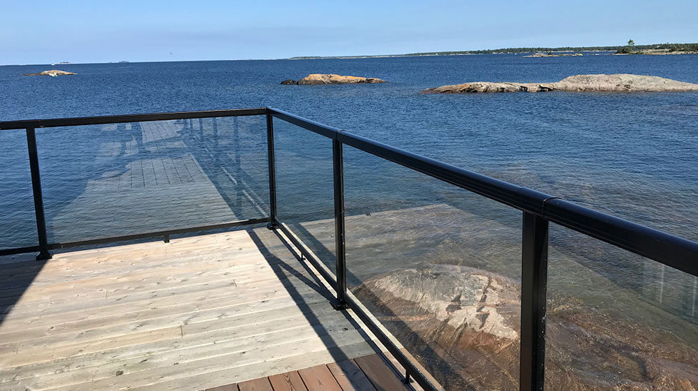 Black Aluminum Railing with Large Glass Panel on Beautiful Deck